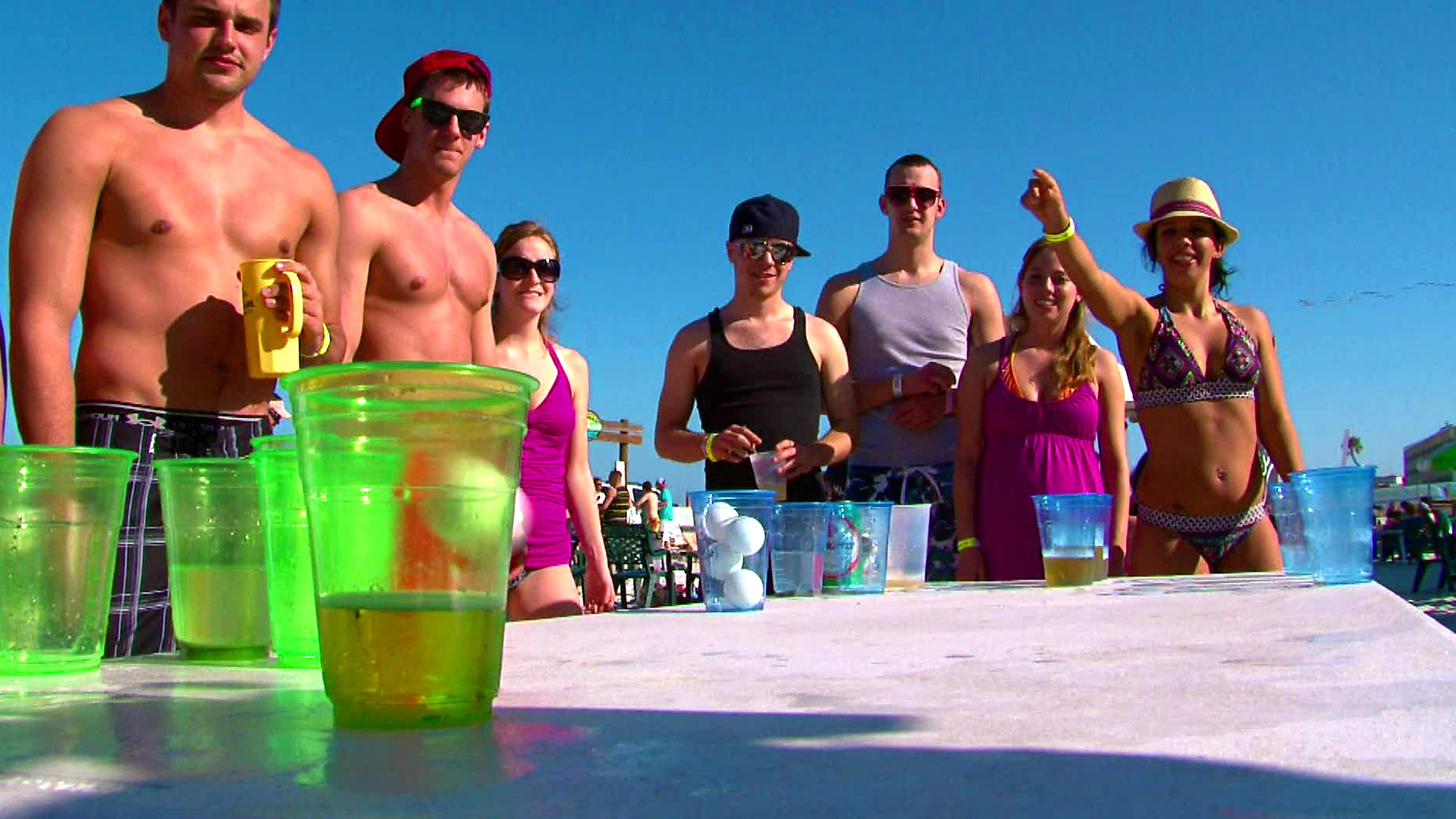 A group of spring breakers playing beer pong.